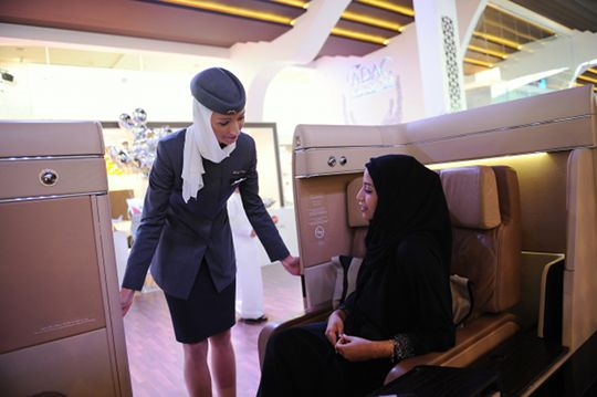 An Etihad flight attendant helps a visitor sit in a mock cabin lounge seat.