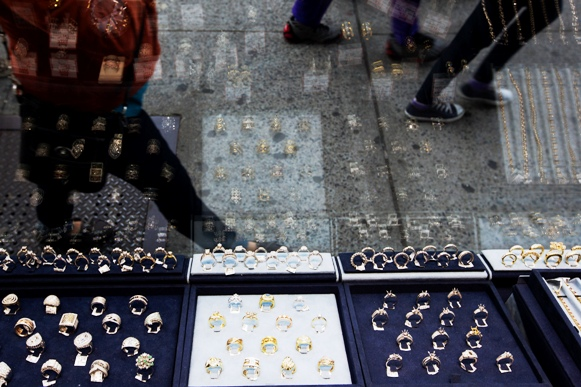 Pedestrians walk past gold and silver jewellery displayed in the window of the Gold Standard jewellery store specializing in purchasing raw gold and silver in New York.