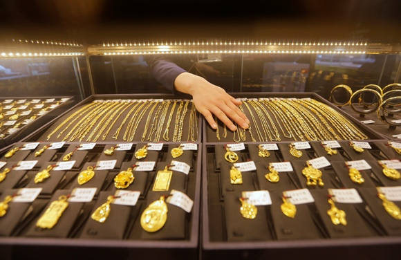 An employee arranges gold jewellery in the counter of a gold shop in Wuhan, Hubei province.