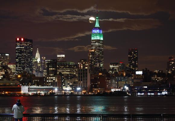 A full moon rises behind the Empire State Building in New York.