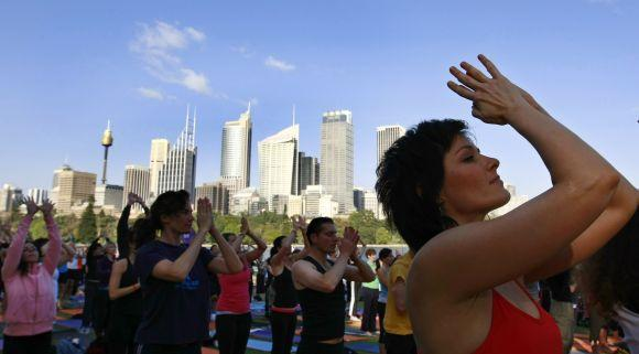 Yoga enthusiasts perform sun salutations in front of the Sydney skyline.