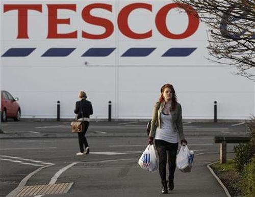 A shopper leaves a Tesco store.