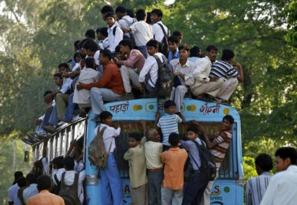 Commuters including school boys travel on a crowded passenger bus during morning rush hours.