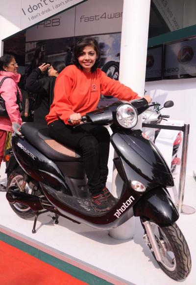 A model sits of Hero Electric's two-wheeler.
