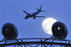 A passenger jet flies past the full moon.