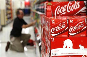An employee arranges bottles of Coca-Cola at a store.