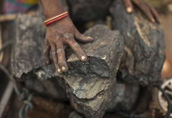 A local woman prepares to carry coal at an open coal field at Dhanbad district.