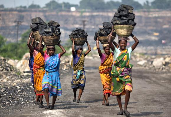 Local women carry coal taken from open cast coal field at Dhanbad district in the eastern Indian state of Jharkhand.