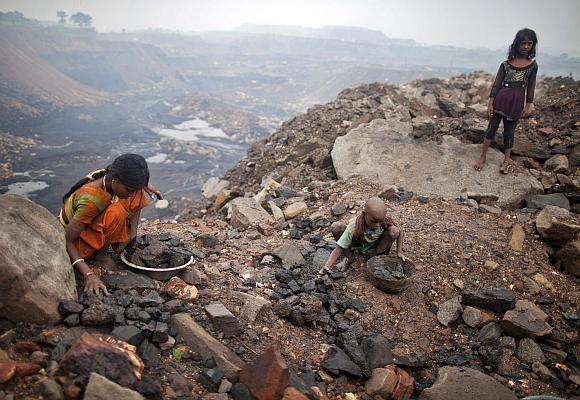 Locals collect coal from an open cast coal field at Dhanbad district in the eastern Indian state of Jharkhand.