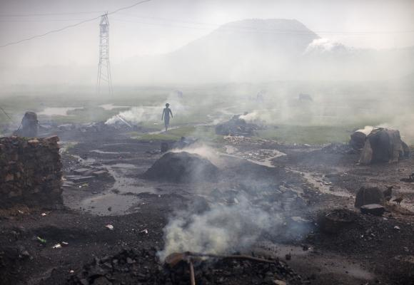 A man walks past heaps of burning coal to make it for domestic use such as for cooking purposes at Dhanbad.