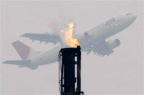 An airplane flies near a gas flare from a factory.