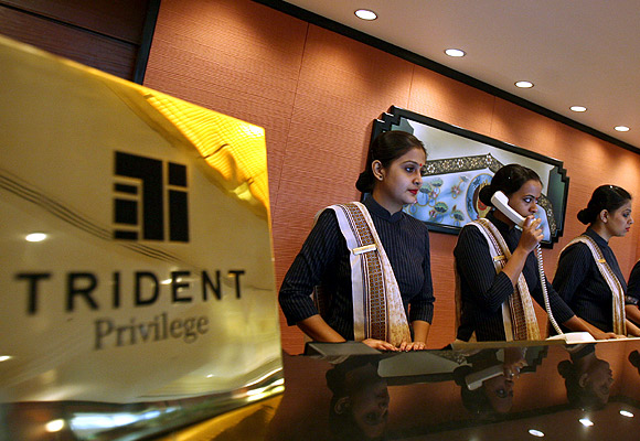 Employees stand at the reception counter of the Trident-Oberoi hotel.