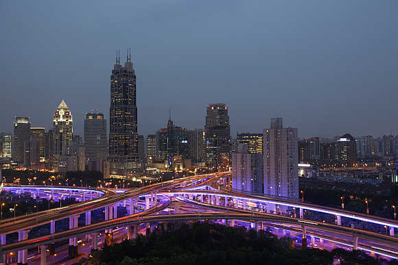 An aerial view shows vehicles travelling on intersections at night in downtown Shanghai, China.