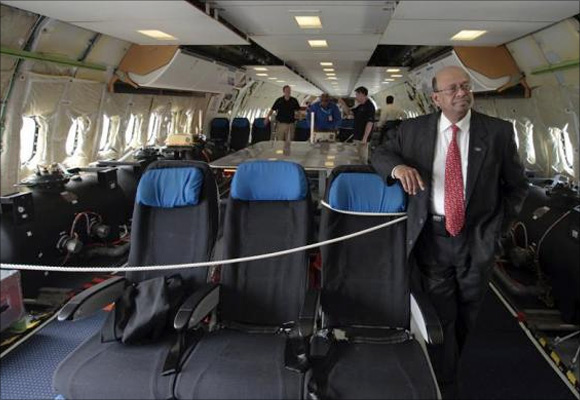 Boeing India President Dinesh Keskar (R) poses as flight technicians work inside the Boeing 787 Dreamliner aircraft for All Nippon Airways (ANA) after its India debut landing at the Indira Gandhi international airport in New Delhi.