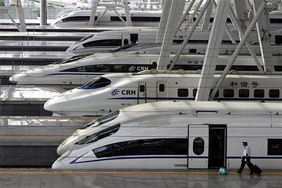 A train employee prepares to enter a CRH (China Railway High-speed) Harmony bullet train at Beijing South Railway Station.
