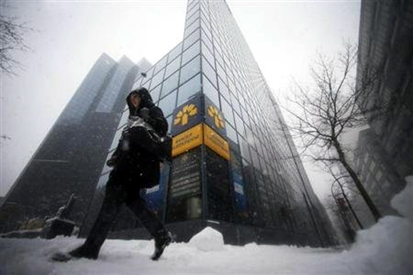 A pedestrian walks past the head offices of Laurentian Bank in Montreal.