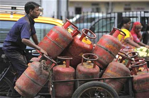 An employee of a cooking gas agency transports gas cylinders on a cart.