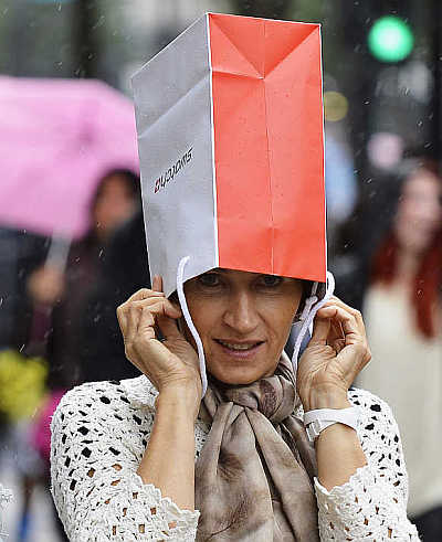 A woman covers her head with a shopping bag to protect herself from rain on Oxford Street in central London, United Kingdom.