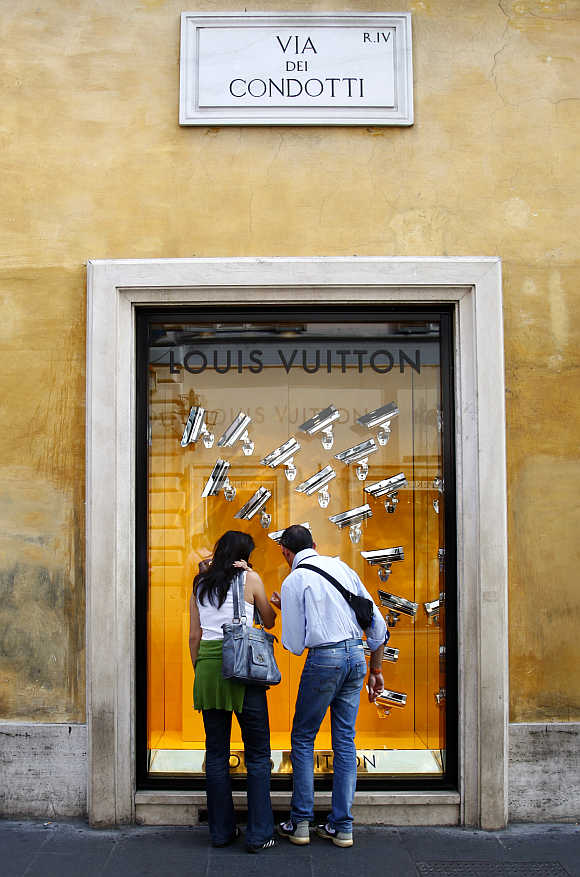 A couple looks at a window display of luxury goods maker Louis Vuitton on the shopping street of Via Condotti in central Rome, Italy.