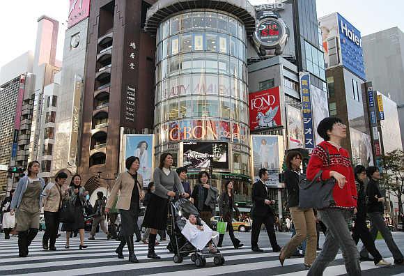 People walk in Ginza street in Tokyo, Japan.