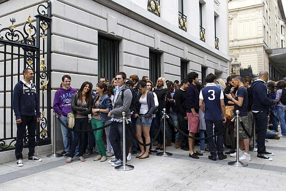 Customers wait outside the Champs Elysees store of clothing retailer Abercrombie & Fitch on its opening day in Paris, France.