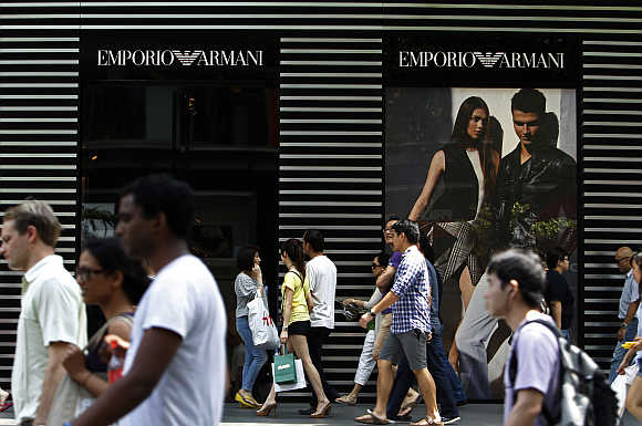 People walk past an Emporio Armani store on downtown Orchard Road in Singapore.
