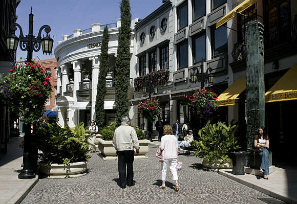 Shoppers walk towards the Versace boutique in Rodeo Drive in Beverly Hills, United States.