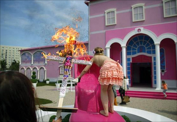 Activists from women's rights group Femen burn a barbie doll on a cross as they protest outside the Barbie Dreamhouse.