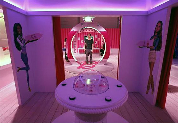 A visitor stands inside a Barbie Dreamhouse of Mattel's Barbie dolls in Berlin.