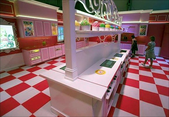 Girls watch the kitchen inside a life-size Barbie Dreamhouse.