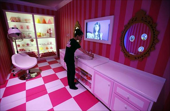 A staff poses for the photographer inside a life-size Barbie Dreamhouse.