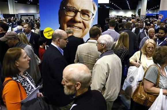 A huge picture of Berkshire Hathaway Chairman Warren Buffett looks over shareholders swarming the exhibit floor where companies owned by Berkshire display and sell their products, at the company's annual meeting in Omaha.