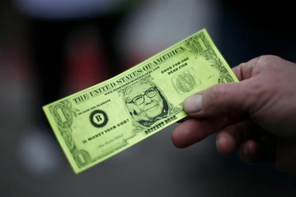 A Berkshire Hathaway shareholder hold a fake dollar bill with the face of billionaire financier and Berkshire Hathaway CEO Warren Buffett during the kick-off celebration at the annual Berkshire Hathaway shareholders meeting in Omaha.