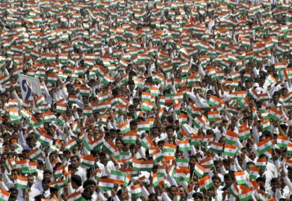 A crowd waves miniature national flags of India.