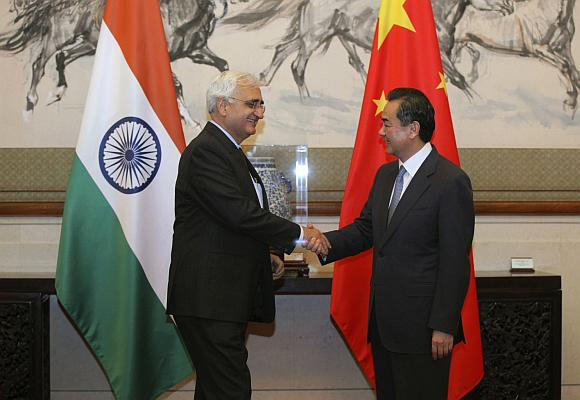 China's Foreign Minister Wang Yi (R) shakes hands with his Indian counterpart Salman Khurshid.