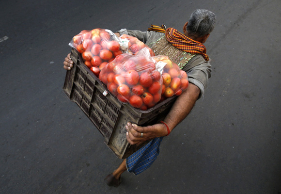 A labourer carrying tomatoes walks along a roadside near a wholesale vegetable market in the old quarters of Delhi.