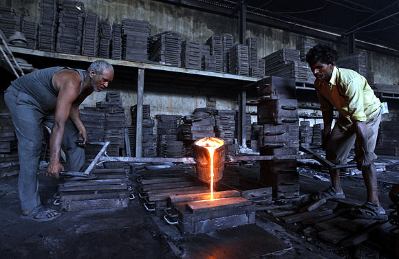 Workers lift a container filled with molten iron inside an iron casting unit at an industrial estate in Ahmedabad.