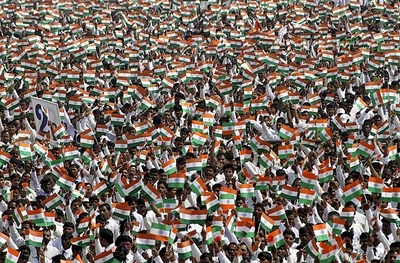 Employees of Sahara Group wave miniature national flags before singing India's national anthem in Lucknow.