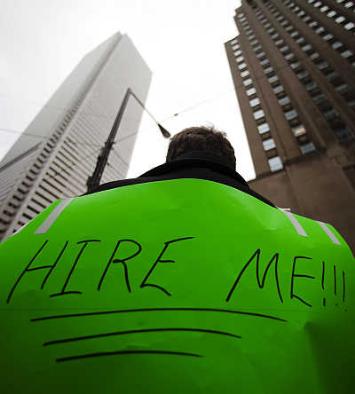 A man, with a sign strapped to his back, uses a megaphone to attract the attention of potential employers as he hands out resumes on Bay Street in the financial district in Toronto, Canada.