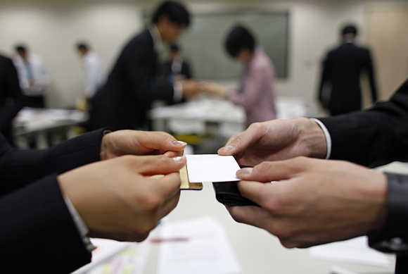 Job-hunting students dressed in suits practice swapping business cards during a business manners seminar at a placement centre in Tokyo, Japan.