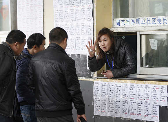 A placement counsellor gestures to job-seekers at a fair in Nanjing, Jiangsu province, China.