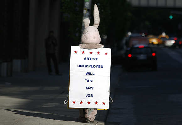 A person dressed as a bunny walks down the street with a sign in New York City.