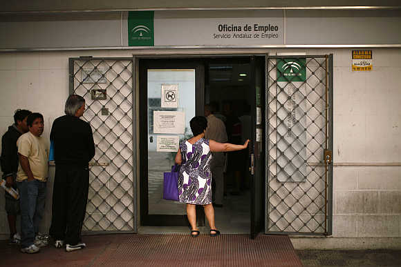 A woman holds a door as she waits in line to enter a government job centre in Marbella, southern Spain.