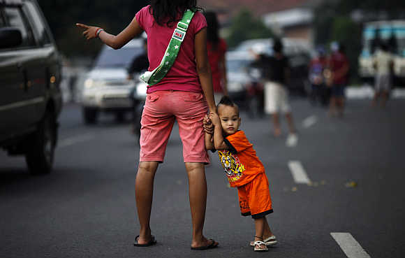A jobless mother holds her child as she offers to be a 'car jockey' in a main street in Jakarta. Many unemployed Indonesians find work as 'car jockeys', for which they are paid around $1.50 to be car passengers, allowing the driver to use a lane dedicated to cars carrying three or more passengers.