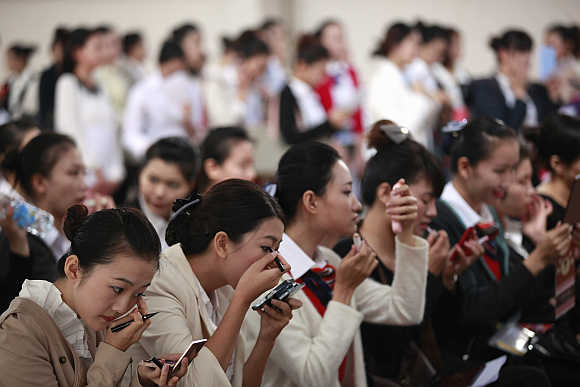 Women apply make-up as they wait during the job fair for China Eastern Airlines flight attendants in Shanghai, China.