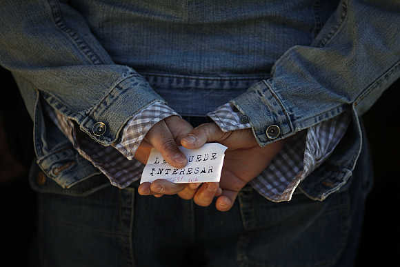 A man holds a paper with a job offer which reads, 'You might want to', as he waits in line to enter a government job centre in Malaga, southern Spain.