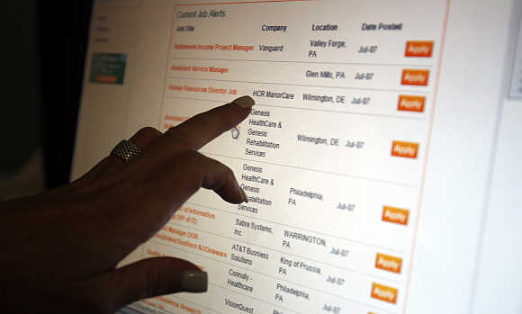 A woman points to a job listing on an employment website.