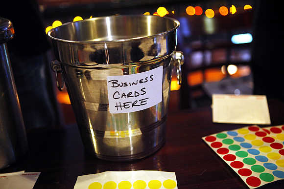 A champagne bucket for members to drop off business cards is displayed as a group of laid-off workers meet during a recruitment event.