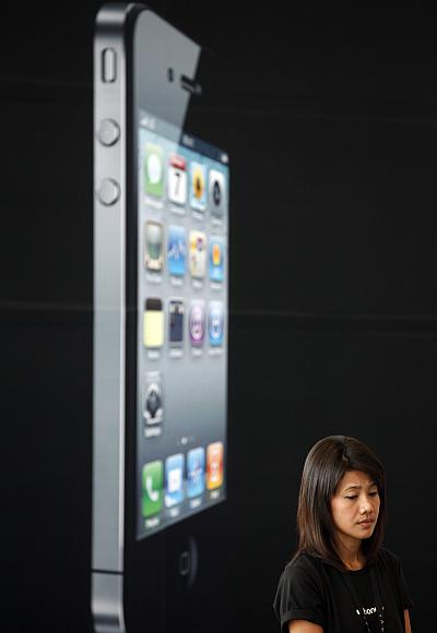 A woman stands next to a giant advertisement for an iPhone in Bangkok.