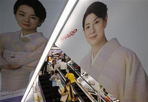 People ride an escalator past Japanese display maker Sharp Corp